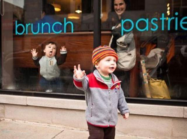 talk to the hand, baby smashing face against restaurant window ~ 18 Funny Awkward Family Photos