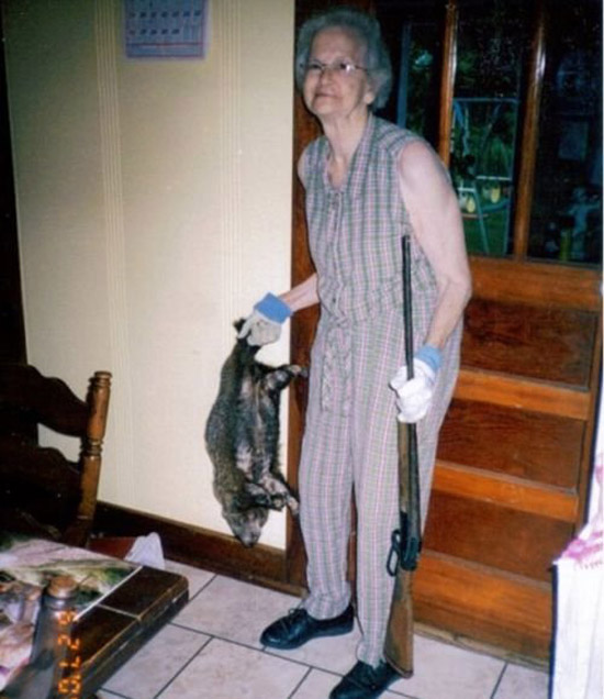 Vintage snapshot of grandma and her gun in kitchen holding a dead varmint for dinner