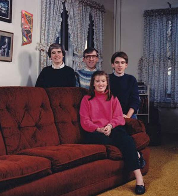 Awkward family portrait with men behind couch