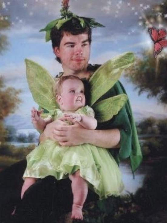 Awkward portrait of man and baby in fairy costumes