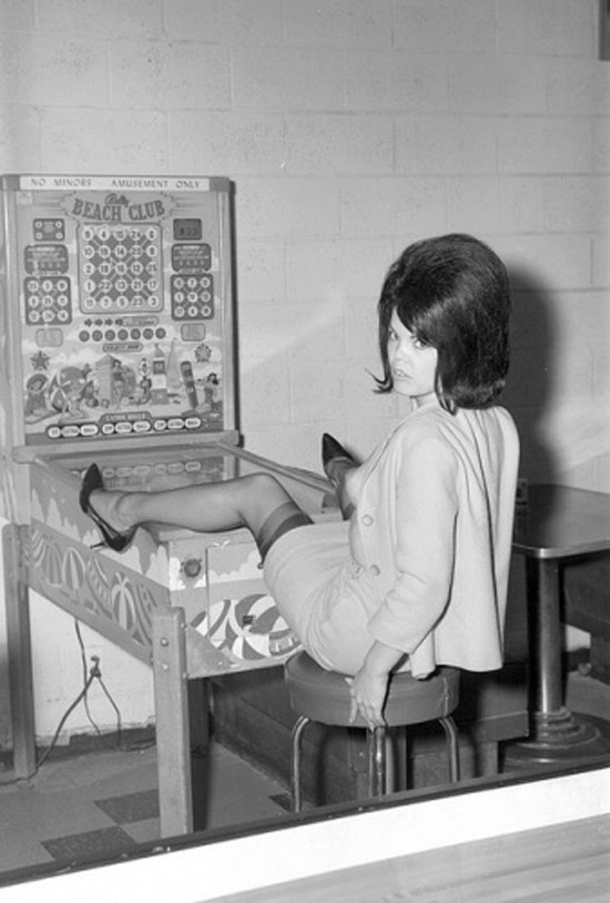 Awkward vintage 1960s snapshot of woman with her legs up on pinball machine, big hair