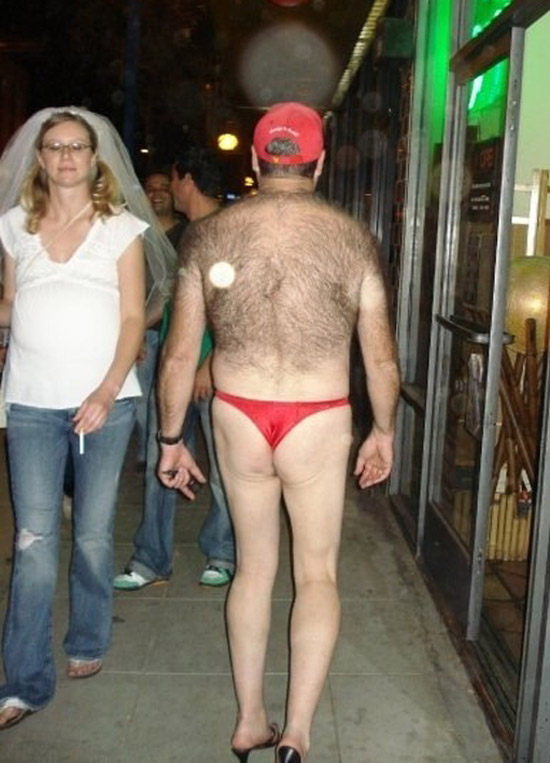 Strange Creepy Awkward photo of man in thong with hairy back walking down the street past a smoking woman in bridal veil and ghostly orbs.