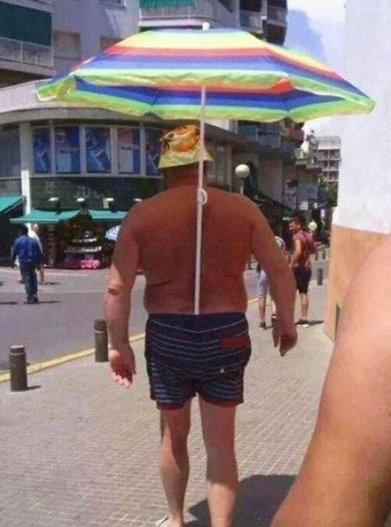 Shirtless man walking down the street in bathing suit with beach umbrella stuck in his suit shading him