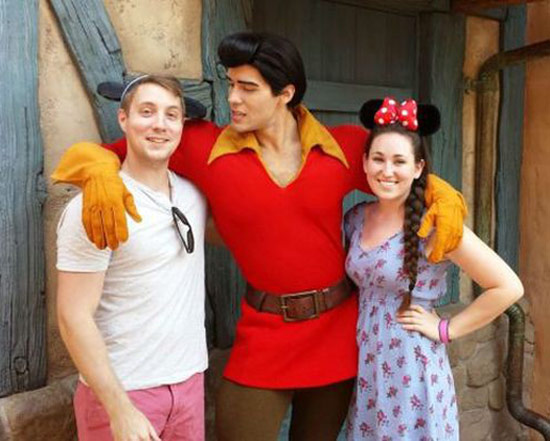 couple at DisneyWorld posting with Gaston who's checking out the guy ~ Awkwardly Funny Family Photos