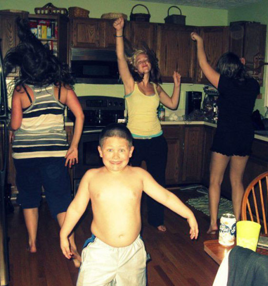 teen girls dancing in kitchen with young little brother, shirtless smiles at camera ~ Awkwardly Funny Family Photos