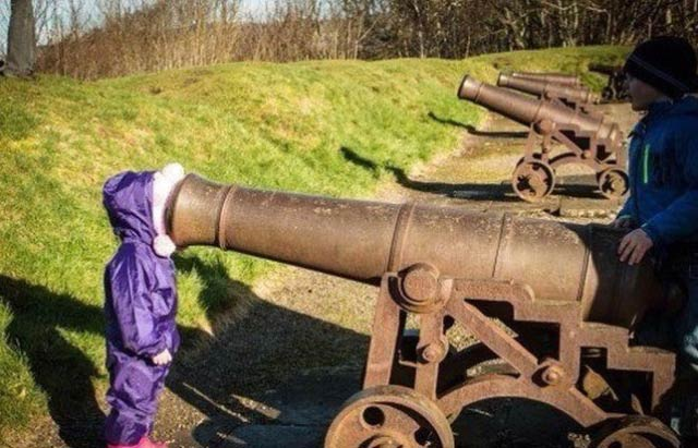 Funny Awkward Family Photos: Kid, girl sticking her face in a cannon