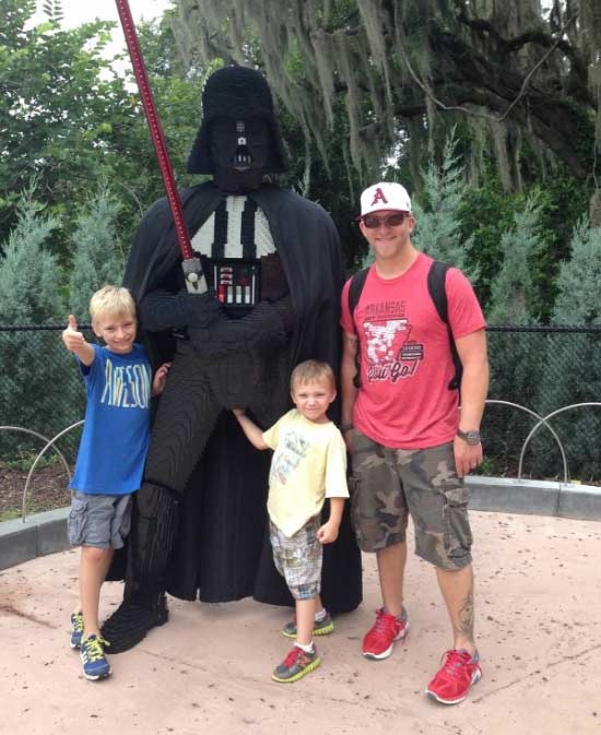 family posing with Darth Vader at Lego Land, little boy has hand in Vader's crtoch