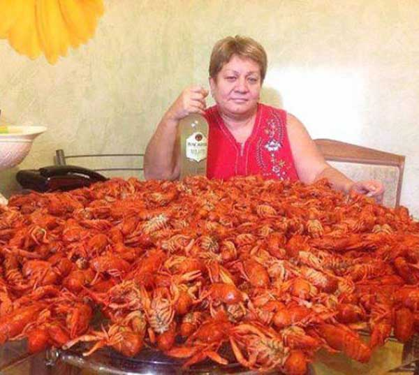 russian woman with bottle of vodka and a table covered full of crawfish