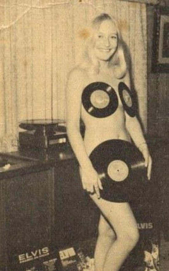 vintage snap of young, naked blonde woman covering herself with Elvis Presley records