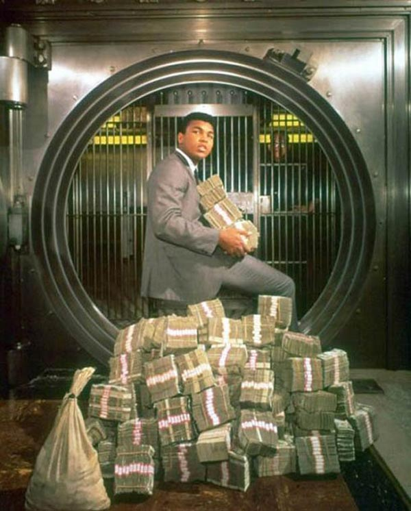 Vintage pic ~ Mohammed Ali sitting on millions of dollars in bank vault