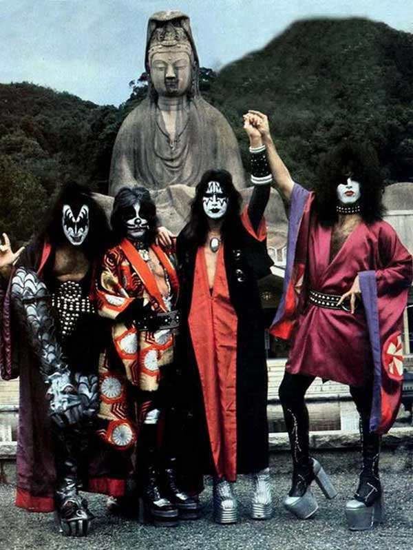 70's rockers Kiss n full make-up in Tibet in front of statue