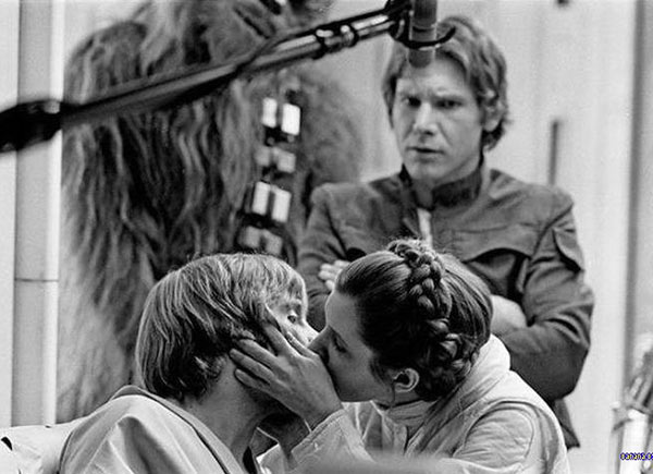 Old picture from firs Star Wars movie set, leah kissing Like with Hans Solo looking on with contempt