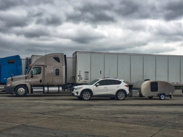 photo of the car and trailer with semi-trailer trucks