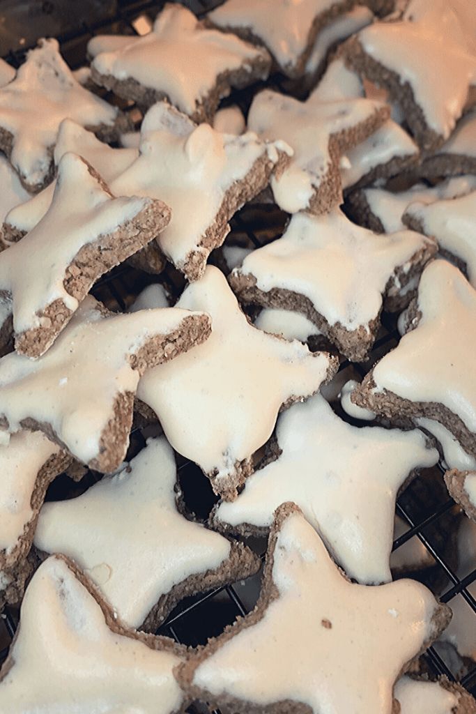 A plate of fresh German cinnamon stars - Zimtsterne - fresh cinnamon stars cooling on a rack - traditional German Christmas baking - the aroma, taste, shape an look makes them the quintessential Christmas biscuit