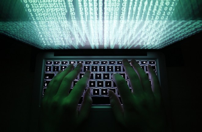 Image: Illustration file picture shows a man typing on a computer keyboard in Warsaw