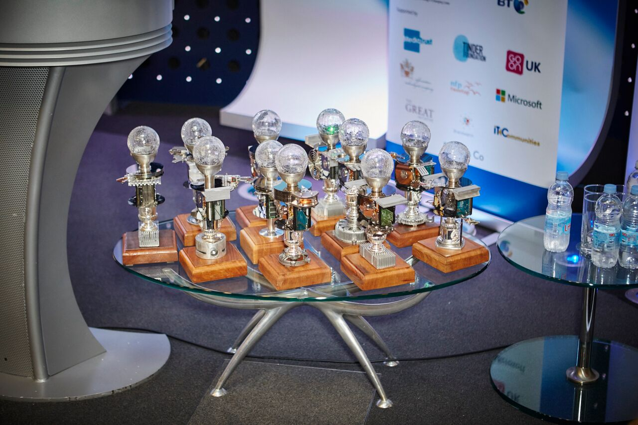 A table of trophies from the Tech4Good Awards 2015