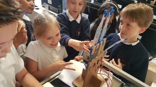 Group of young children working together on a computing project