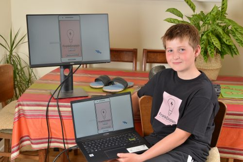 Young boy Otto Sutton sitting in front of screens showing the FrankEinstein logo