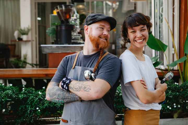 Couple of smiling barista coworkers in casual outfit and aprons standing with portafilter near cafeteria in street near plants in daylight