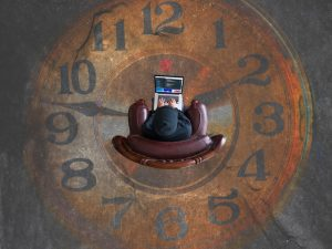 person on a laptop on a clockface