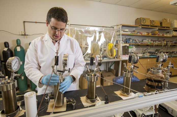 Giammar assembles a stainless steel pressure reactor in his lab. The reactor was designed to simulate conditions deep underground, and test how much CO2 basalt can trap and convert within its pores. (Photo: Joe Angeles/Washington University)