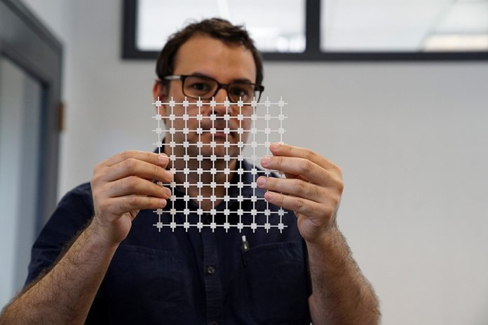Jose Gomez-Marquez, co-director of MIT's Little Devices Lab, holds a sheet of paper diagnostic blocks, which can be easily printed and then combined in various ways to create customized diagnostic devices.