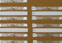 An RFID tag is modified by cutting out a small part its antenna (silver ribbon) and placing a small light-sensing phototransistor or temperature-responsive resistor (thermistor) on it. CREDIT University of Waterloo