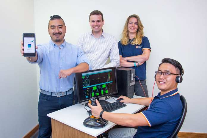 Prof Dean Ho (first from left) showing a schematic mobile version of CURATE.AI, while Mr Theodore Kee (seated) demonstrates the flight operations simulator software. With them are Asst Prof Christopher L. Asplund (second from left) and Dr Agata Blasiak (third from left). Credit: National University of Singapore