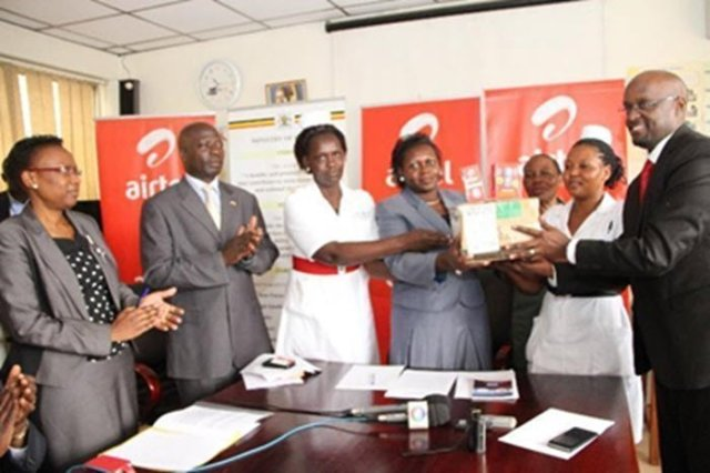 Airtel Legal & Regulatory Director, Mr. Dennis Kakonge hands over 150 phones to the Hon Minister of Primary Health Care,   Hon Sarah Opendi as ministry officials look on.