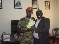 NITA's James Saaka hands over copies of all the laws that governs the Uganda cyberspace to Brigadier Sabiiti.