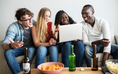 Group of diverse friends hanging out and using digital devices