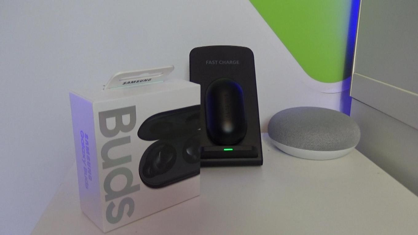 A picture of the Galaxy Buds box alongside the Buds themselves on a wireless charger