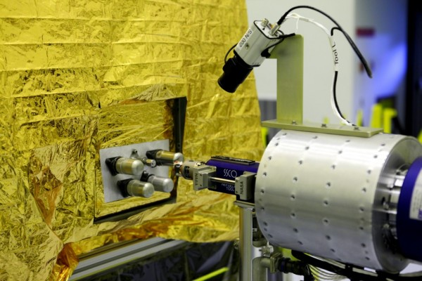 Commanded from NASA's Goddard Space Flight Center in Greenbelt, Md., the RROxiTT industrial robot connects to a simulated satellite fill and drain valve located in the Payload Hazardous Servicing Facility at the Kennedy Space Center in Florida. The test was to demonstrate how future satellite servicing spacecraft could transfer oxidizer to a satellite not designed to be refueled. Image Credit: NASA