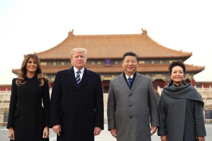 Donald Trump, MelaniaTrump, Xi Jinping and Peng Liyuan stand in front of a Forbidden City palace.