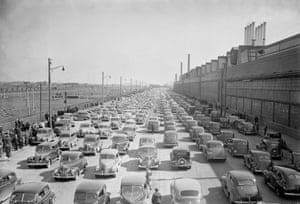 Sightseeing motorists pass the Ford River Rouge Plant in Detroit in 1941 – to look at strikers' picket lines.