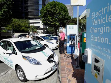 FILE- In this July 28, 2015, file photo, a line of electric cars and newly installed charging stations are seen in front of the Portland General Electric headquarters building in Portland, Ore. Portland General Electric has pledged to build 36 electric vehicle charging stations in Portland, Milwaukie and Hillsboro opening sometime in early 2019, with the next three yet-to-be-determined sites to open later in the year. (AP Photo/Don Ryan, File)
