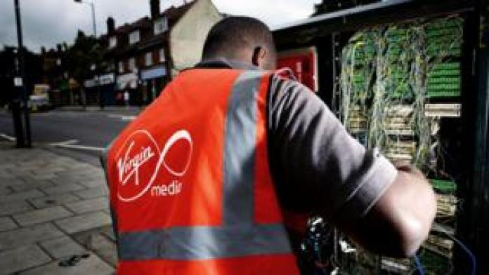 A Virgin Media technician works on the cabling in a roadside cabinet