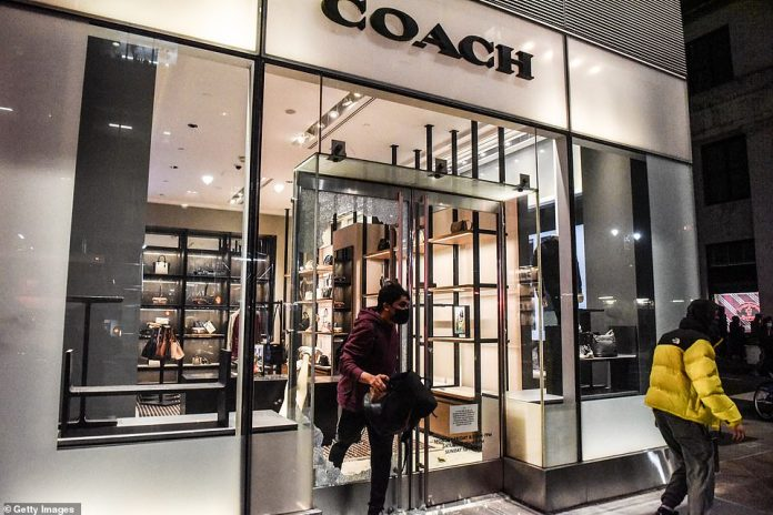 Looters pictured running out of a vandalized Coach store in Manhattan on Sunday