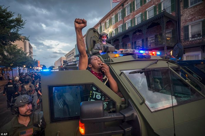 SAVANNAH, GEORGIA:Protester Kendrick Cutkelvin of Savannah uses a SWAT vehicle loudspeaker to disperse a small crowd of protesters after a peaceful protest in Georgia last night