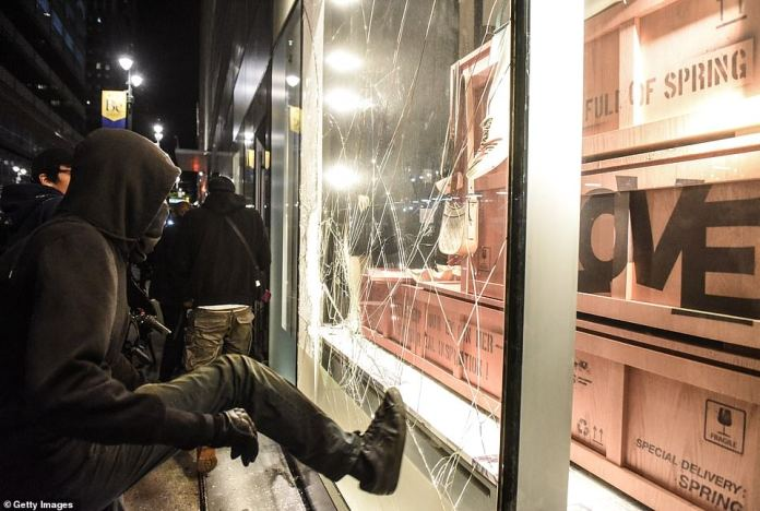 NEW YORK CITY: A hooded man tries to smash a window in New York where protests continued following George Floyd's death at the hands of Minneapolis police a week ago
