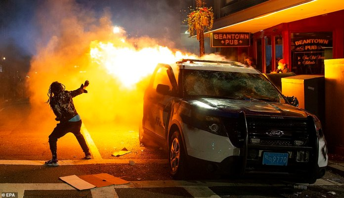 A man tries to light a cigarette from the flames engulfing a Boston Police cruiser during clashes in Massachusetts last nihgt