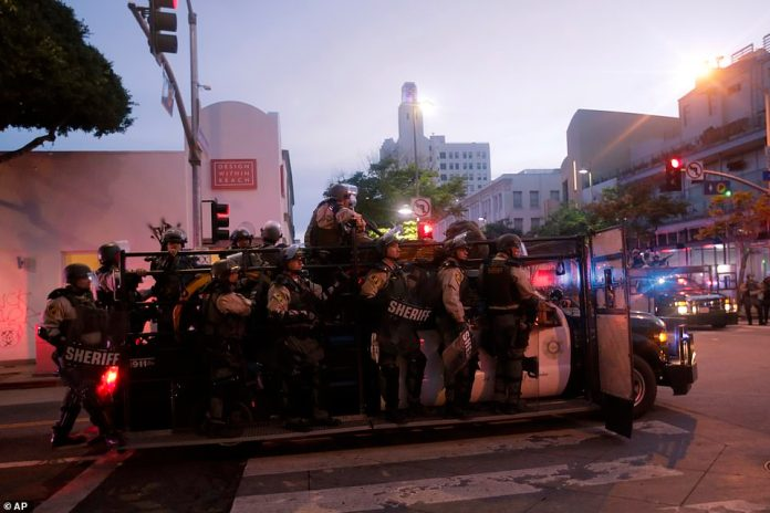 Los Angeles County Sheriff's officers patrol Sunday in Santa Monica, California after peaceful protests turned into mass lootings