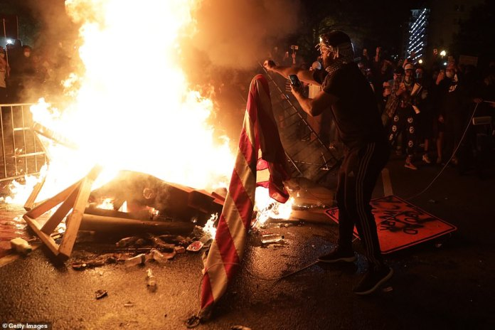 Demonstrators prepare to burn a US flag at a protest near the White House on another night of protests across the country