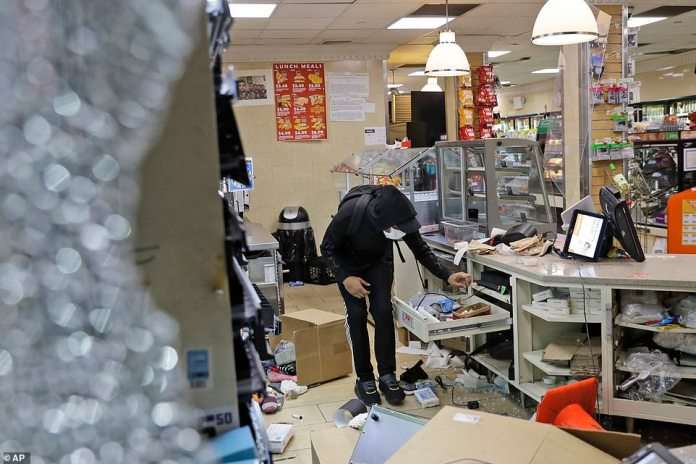 Protesters pictured ransacking a 7-Eleven store in New York late Sunday