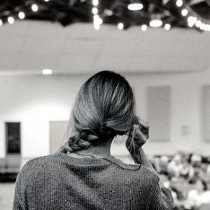 A woman on stage with her back to the camera