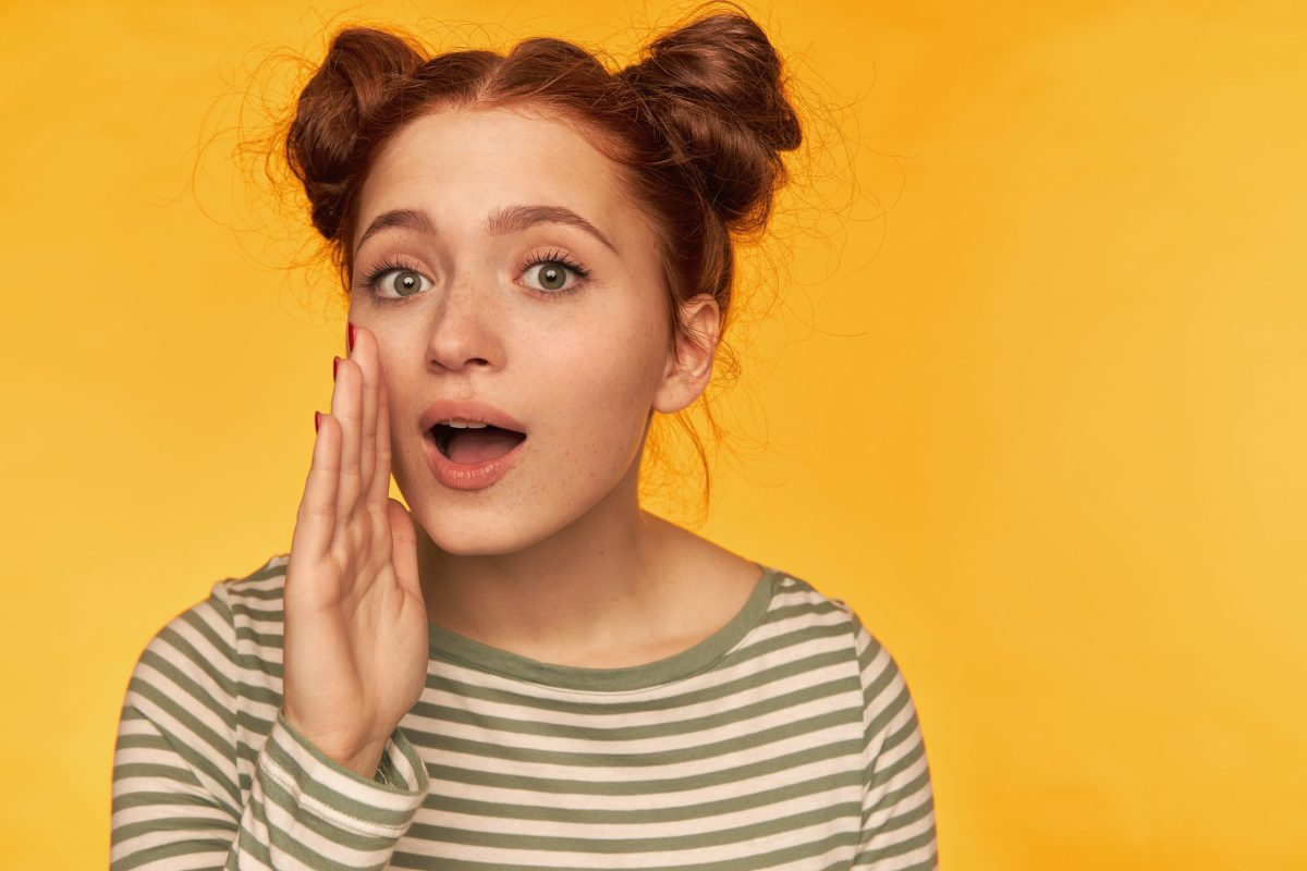 teenage girl happy looking red hair woman with two buns wearing striped blouse holding hand her mouth whisper you isolated yellow wall scaled Twin Front