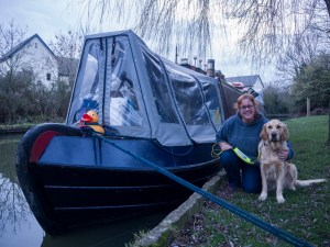 Golden Retriever sitting with 'Ma' kneeling beside him. They are both beside the bow of the narrowboat, which has a silver-grey cratch cover (this is a canvas cover over the bow deck with clear plastic windows in the sides and front). Arnold the giant yellow bath duck is sitting on the top of the very front of the boat