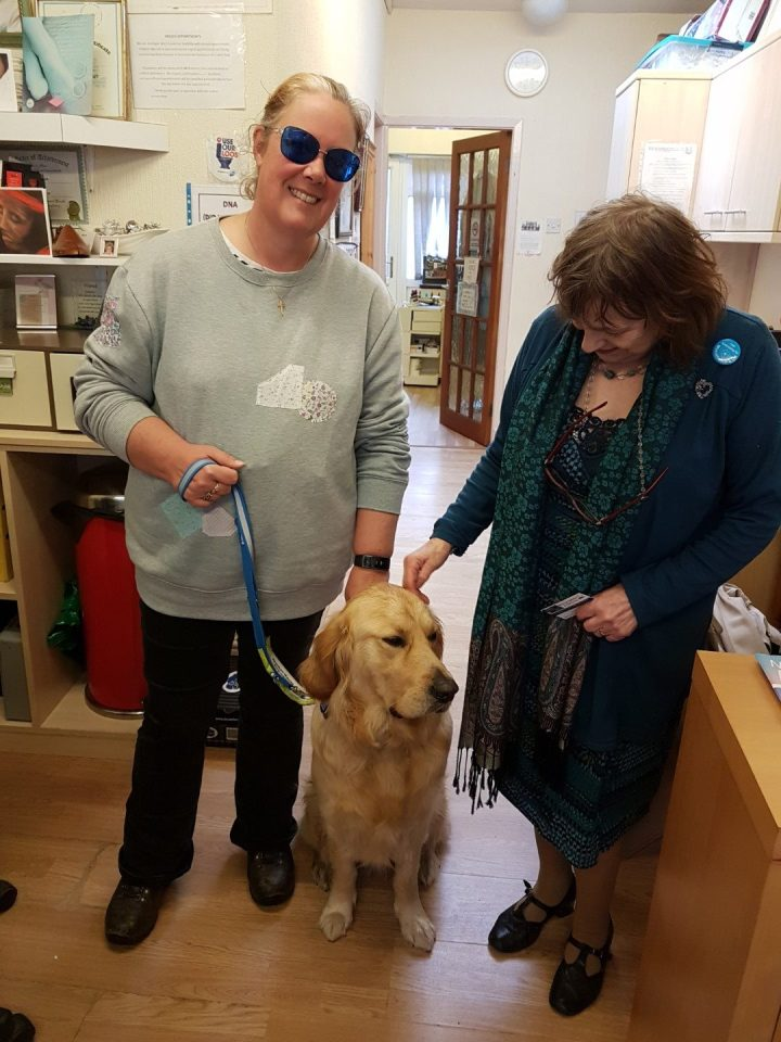 from left to right - Mummy standing, Teddy sitting, Chiropodist lady standing stroking Teddy's head. All on wooden floor with desk beside