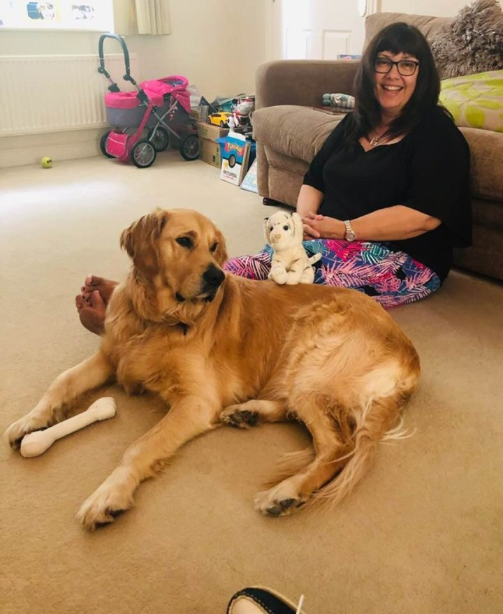 Teddy lying on cream carpet beside MummyAndi who is sitting on the floor leaning against a biege sofa. Teddy has a white bone-chew between his front paws and a cuddly toy behind him on Andi's lap