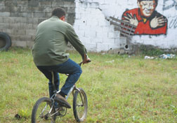 "Venezuelan President Hugo Chavez rides a bicycle in his grandmother's backyard in the Oliver Stone documentary ""South of the Border."""